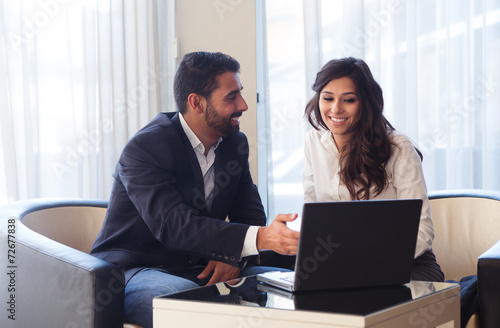 Leinwanddruck Bild Business couple with computer