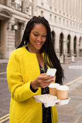 young woman reading a text message and holding coffee's.