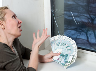 housewife cries and counts money for repair of a window
