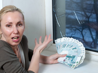 The housewife cries and counts money for repair of a window