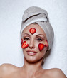 beautiful young woman in towel with a strawberry mask