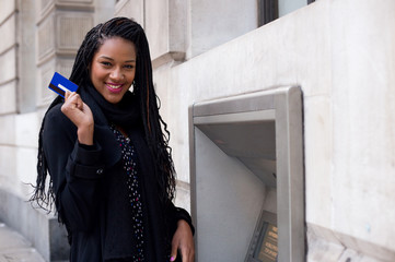 a happy young woman holding a cash card at a cash mashine.