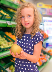Little girl with apple in grocery store.
