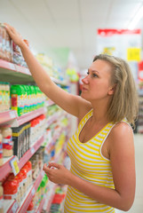 Young woman choosing pasta in grocery store.