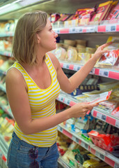 Young woman choosing meat in grocery store.