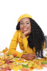 Hübsche schwarze Frau in Herbstblättern isoliert
