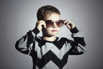 Fashionable little boy in sunglasses and sweater.Stylish Child