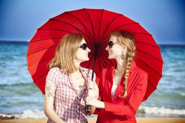 Hermanas gemelas bajo sombrilla roja