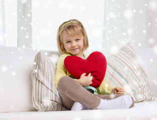 smiling girl with big red heart sitting on sofa