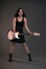 Teenage rock girl with electric guitar. Wearing black dress.