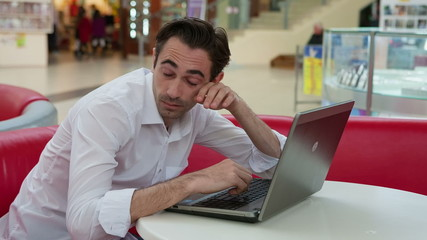Exhausted businessman working with his laptop at table in patio
