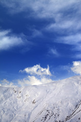 Off-piste slope and blue sky with clouds