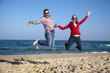 Pareja saltando en la playa
