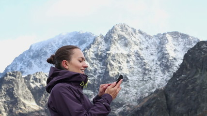 Woman texting on her mobile phone in the mountains