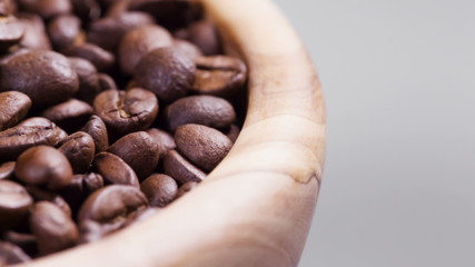 close up footage of rotating roasted coffee beans in wood bowl,