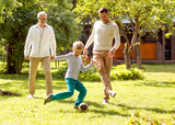 Fototapety happy family playing football outdoors