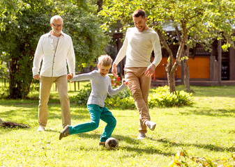 happy family playing football outdoors