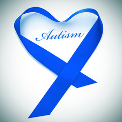 word autism and blue ribbon forming a heart
