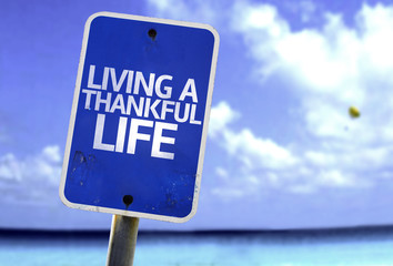 Living a Thankful Life sign with a beach on background