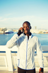 Attractive runner using mobile phone after fitness training