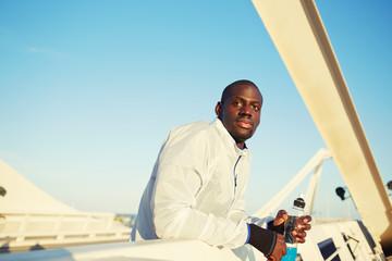 Handsome jogger leaning on bridge fence rest after jog,