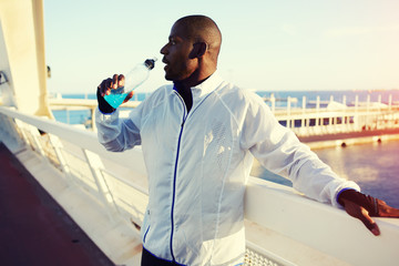 Male runner drink energy drink resting after intensive run