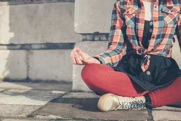 Young woman meditating in the street