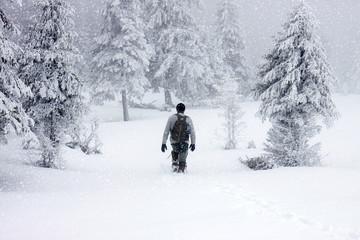 man trekking in foggy winter landscape