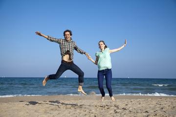 Pareja de novios saltando alegre en la playa