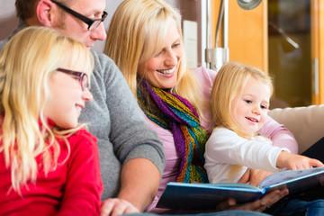 Familie beim Geschichten vorlesen am Abend