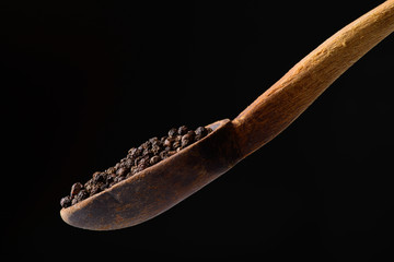 black pepper in wooden spoon