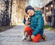 Little boy with beagle on the autumn street