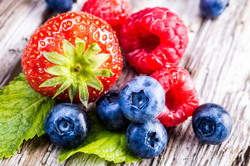 Berry fruits on wooden background or table.