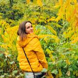 Cute woman in yellow hoody walking in autumn forest.