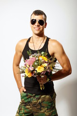 Young soldier in sunglasses standing holds bouquet of flowers