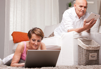 mature couple reading news in digital devices