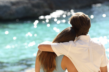 Couple hugging and watching the sea on holidays