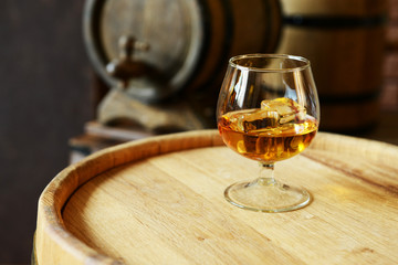 Glass of brandy in cellar with old barrels