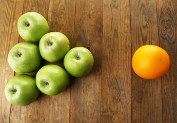 Juicy apples and orange on wooden table