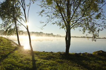 sunrise and morning mist on summer end lake