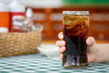 Hand holding glass of cola drink on table