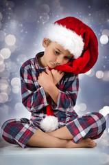 Junge mit Nikolausmütze im Schlafanzug