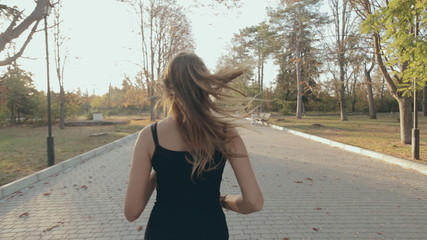 Athletic girl runs through the empty park