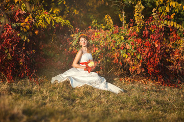 Bride sitting in autumn bush