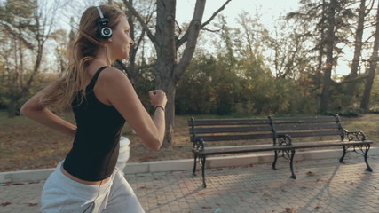 Beautiful girl listening to music on headphones and runs through