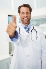 Smiling male doctor gesturing thumbs up at medical office