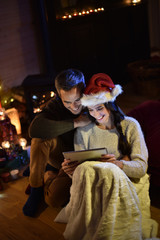 Romantic couple sharing a digital tablet near a wood stove on a