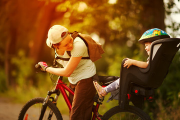 Young woman on a bicycle with little daughter  behind