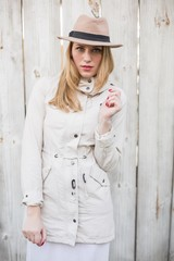 Cute blonde woman with hat posing while looking at camera
