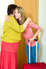 mother hugging  daughter near the door